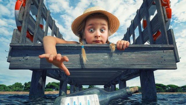 Девочка ловит бутылку с запиской из моря