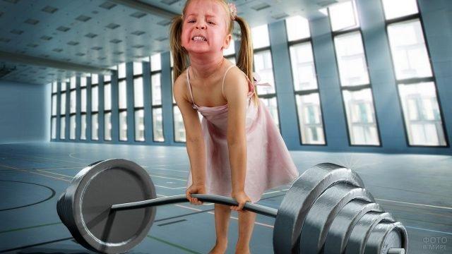 Девочка поднимает штангу в спортзале