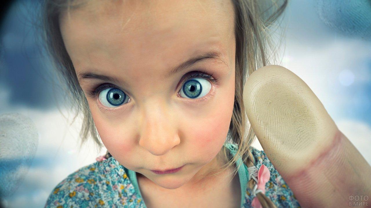 Девочка с красивыми глазами показывает пальчик