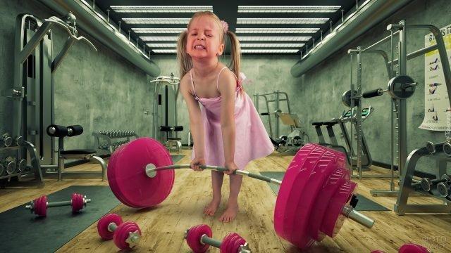 Девочка с усилием поднимает розовую штангу