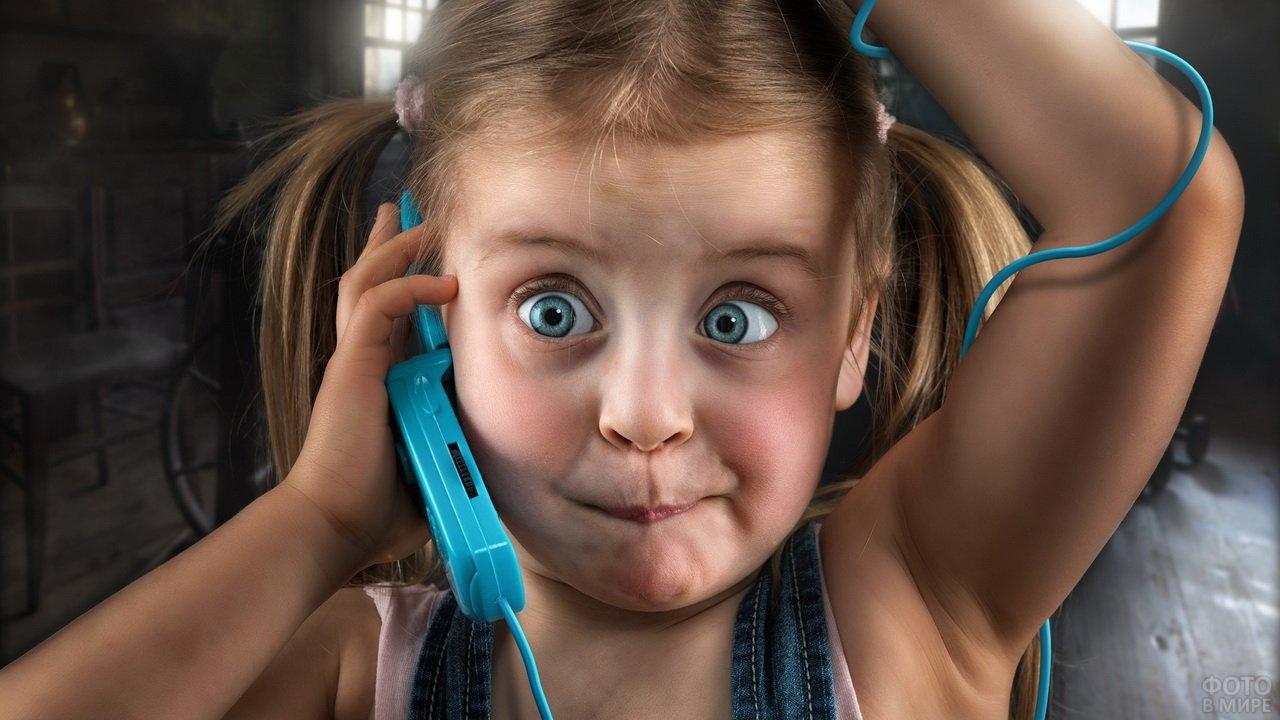 Девочка с забавной мордашкой звонит по телефону