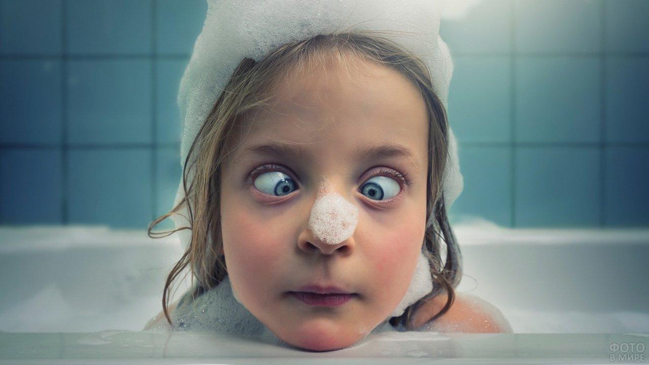 Девочка скосила глаза и смотрит на пену на своём носу