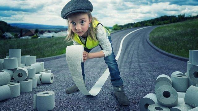 Девочка туалетной бумагой делает дорожную разметку