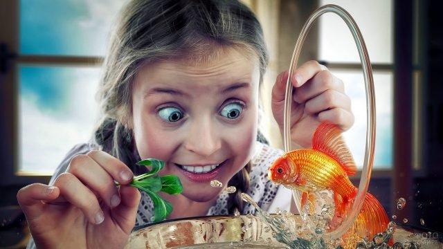 Девочка учит золотую рыбку прыгать через кольцо