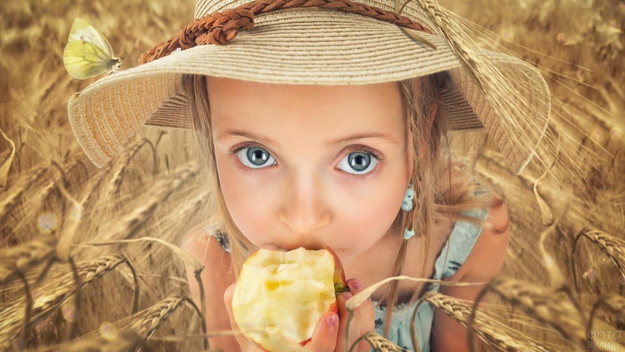 Девочка в шляпе с красивыми глазами ест яблоко