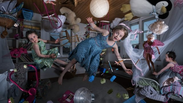 Девочки вместе с игрушками летают в комнате в невесомости