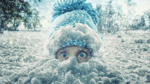 Глаза маленькой девчушки, смотрящие из сугроба