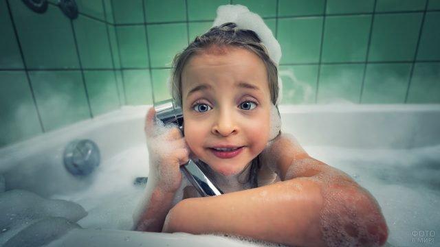 Маленькая девочка в ванной говорит в душ как в телефон