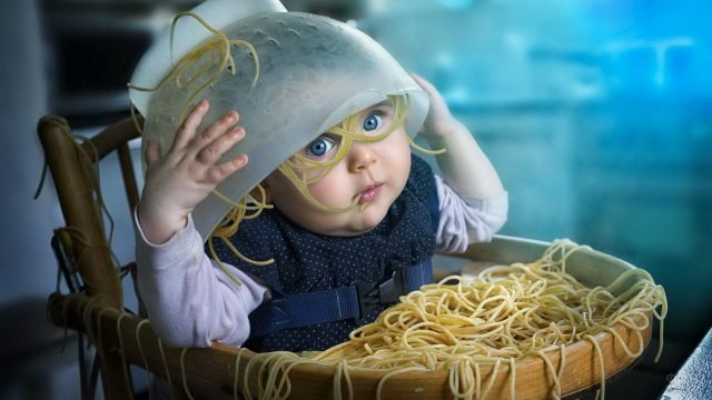 Маленькая голубоглазая девочка вывалила на себя спагетти