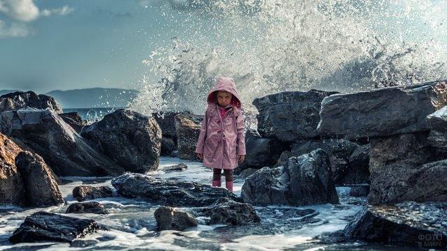 Обиженая девочка среди камней на фоне морской волны