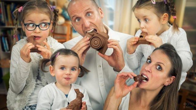 Папа с мамой и три дочки едят шоколадные фигурки