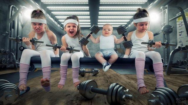 Три девочки и малыш в спортзале с гантелями