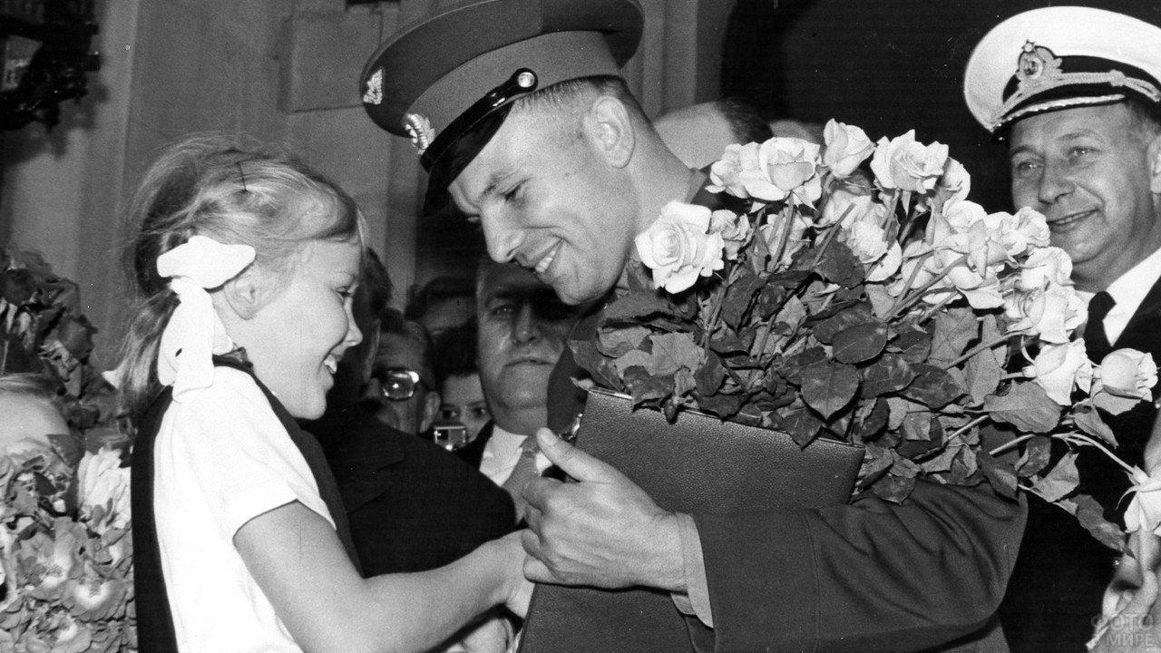Космонавт Юрий Гагарин принимает цветы от советской школьницы