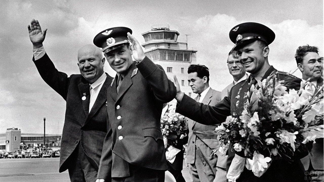 Космонавты Юрий Гагарин с цветами и Герман Титов в окружении первых лиц государства