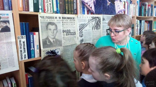 Современные школьники рассматривают портрет Юрия Гагарина на передовице 1961 года