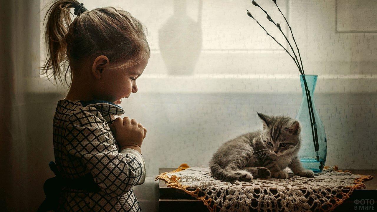 Девочка и котёнок, который лежит на столике