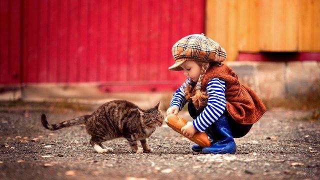 Девочка кормит кошку батоном