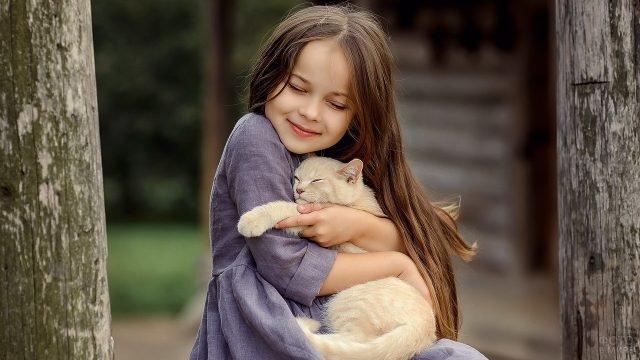 Девочка крепко обнимает свою кошку