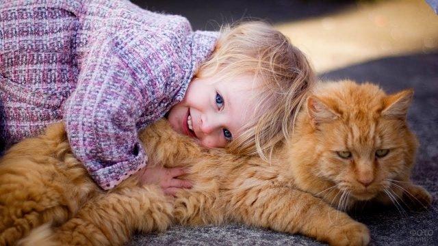 Девочка обнимает рыжего кота