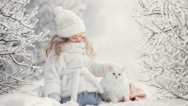 Девочка с белым котом в снежном лесу.