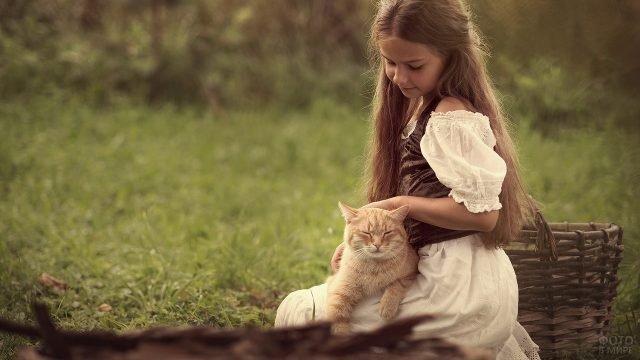 Девочка с корзиной гладит кошку у себя на коленях