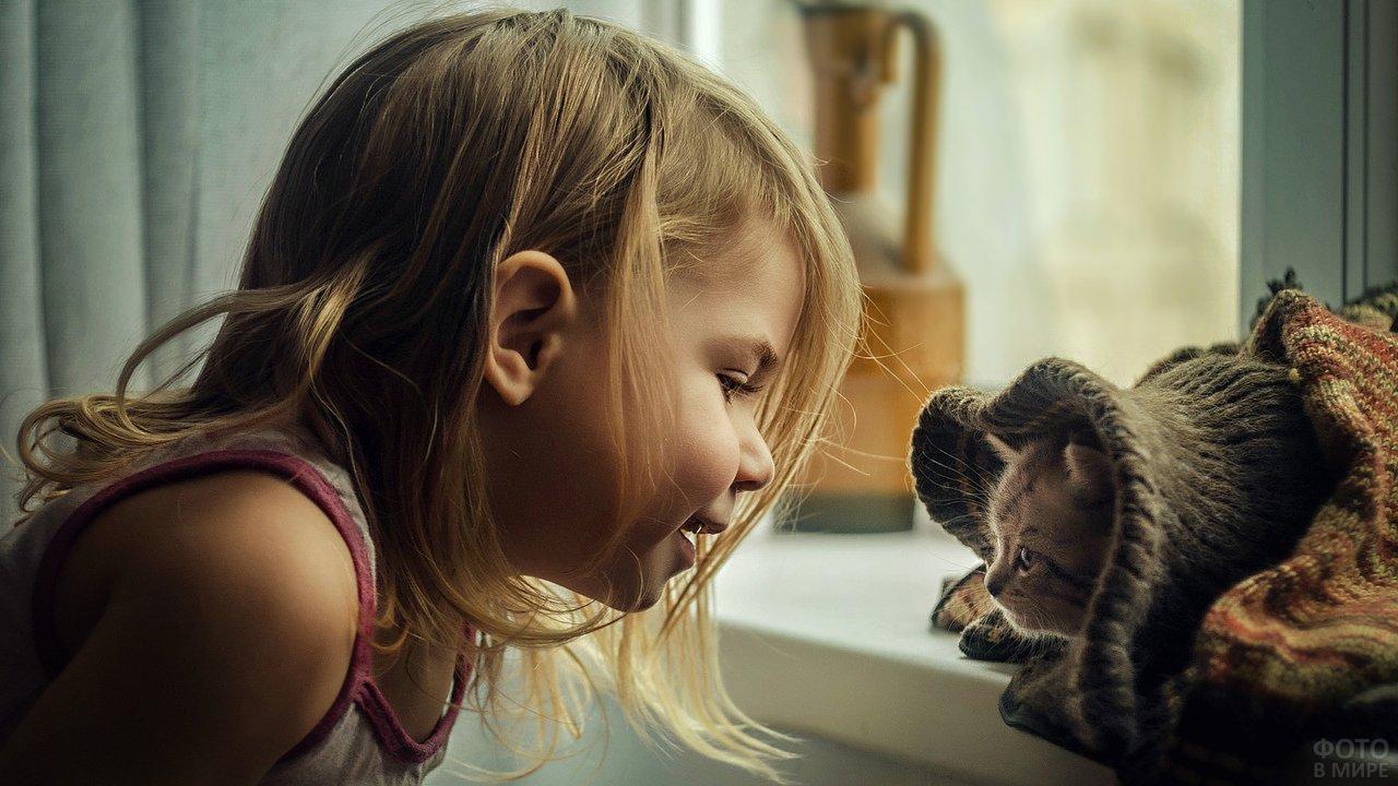 Девочка с котёнком, завёрнутым в шарф