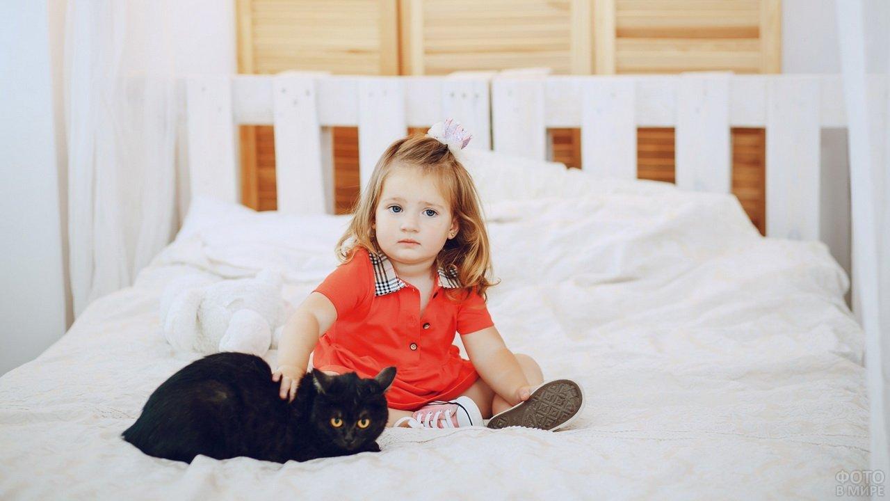 Девочка сидит на кровати с чёрной кошкой