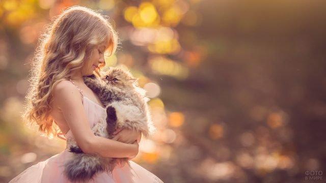 Девочка в красивом платье держит пушистого кота