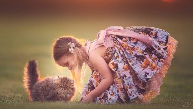 Девочка в платье с котятами играет с котом