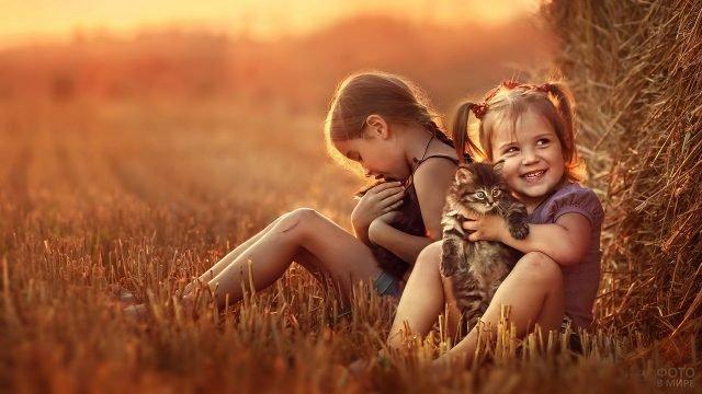 Две девочки с котятами возле сена