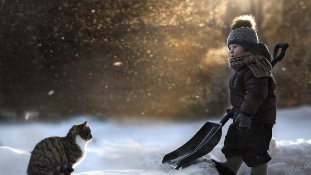 Мальчик с лопатой и котом на снегу