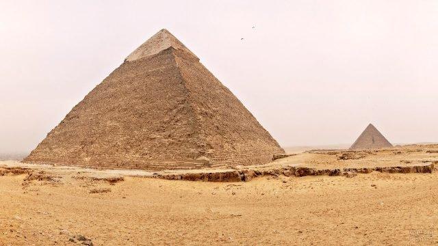 Две птицы словно маленькие точки на фоне могучей пирамиды