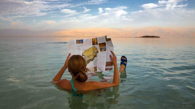 Туристка в плотной солёной воде Мёртвого моря на курорте в Иордании