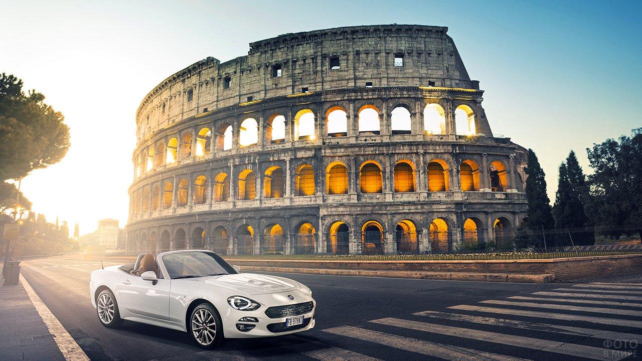 Белый кабриолет у подножья римского Колизея в косых лучах солнца