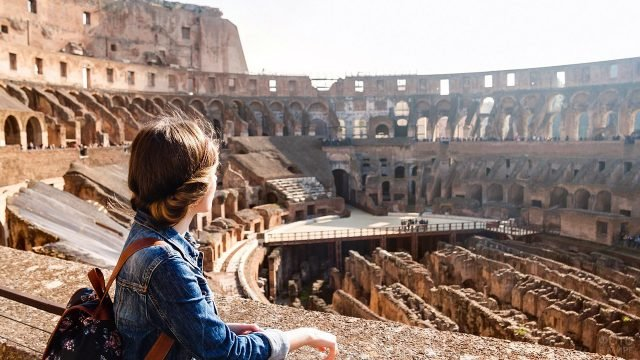 Девочка смотрит на арену Колизея в Риме