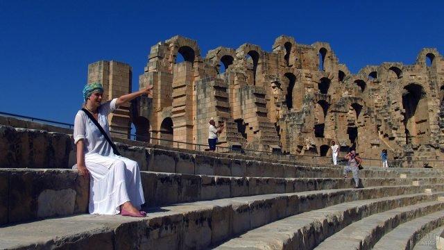 Туристка на ступенях амфитеатра в Тунисском колизее