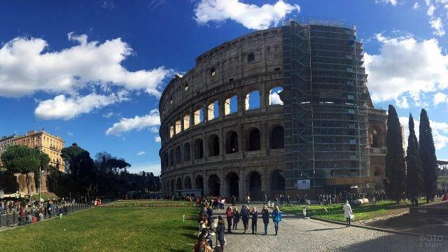 Туристы на панораме Рима с Колизеем в строительных лесах