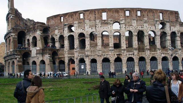 Туристы у подножья Колизея в осеннем Риме