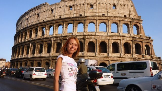 Улыбающаяся девушка на фоне Колизея в Риме