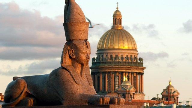 Сфинкс в лучах заката над Санкт-Петербургом на фоне Исаакиевского собора