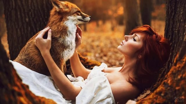 Девушка в осеннем лесу лежит посреди деревьев с лисою на руках