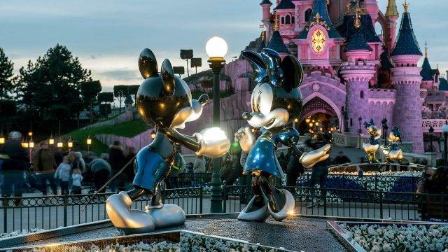 Светящаяся огнями статуя Микки и Минни в вечернем Парижском Диснейленде