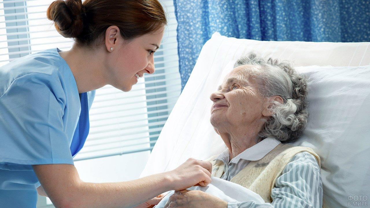 Медсестра склонилась к престарелой пациентке больницы