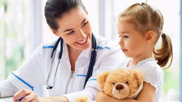 Молодая врач-педиатр разговаривает с маленькой девочкой