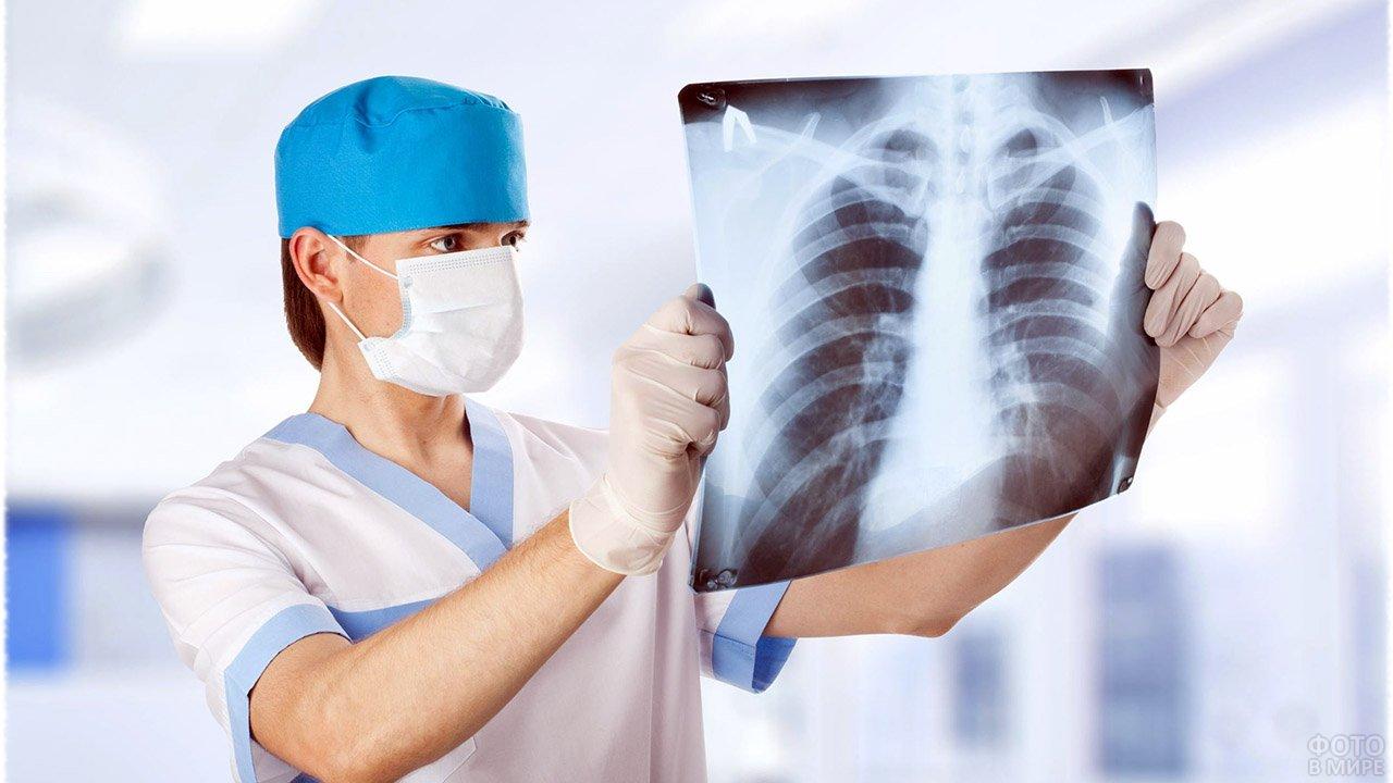 Молодой врач в маске смотрит на рентген-снимок грудной клетки