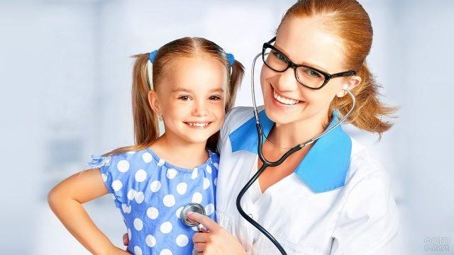 Улыбающиеяся девушка-педиатр и девочка с хвостиками