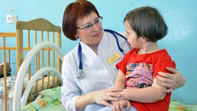 Заслуженный педиатр в детском отделении больницы с девочкой на коленях