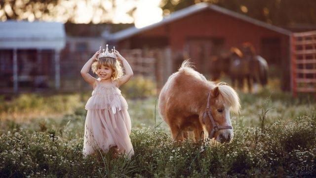 Девчушка надевает корону рядом с пасущимся пони