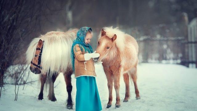 Девочка в нарядном платке и шубке рядом с пони зимой