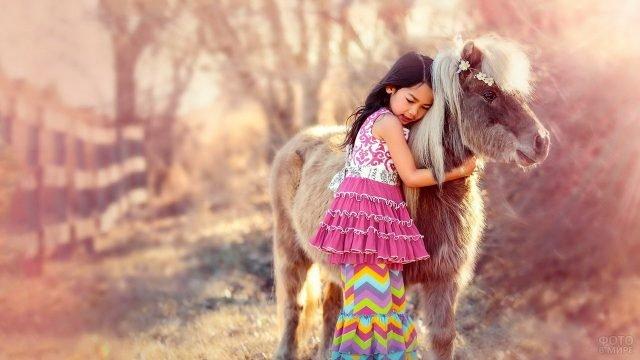 Девочка в розовом платье обнимает пони